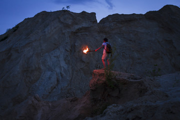 Caucasian man holding torch under rocky cliff