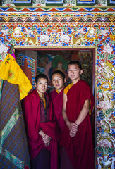 Asian monks standing in temple doorway