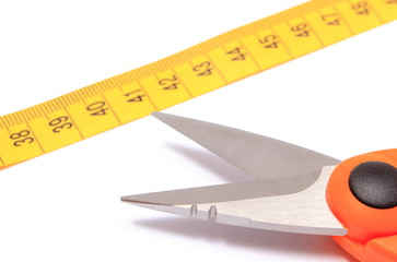 Scissors with tape measure on white background