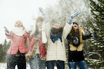Caucasian girls tossing snow in air