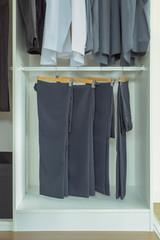 Men slacks hanging in white wardrobe