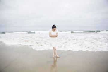 Woman standing near waves on beach