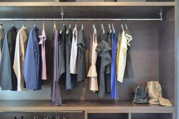 Stylish cloths in dark shade hanging in open wooden wardrobe