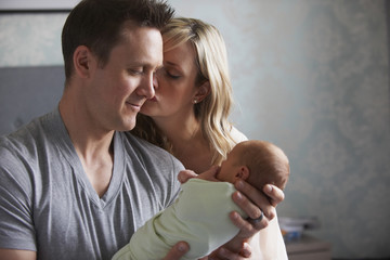 Caucasian parents admiring newborn