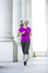 Caucasian woman jogging outside courthouse