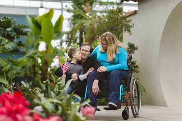 Paraplegic woman and family hugging in garden
