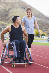 Paraplegic athlete in wheelchair with girlfriend on track