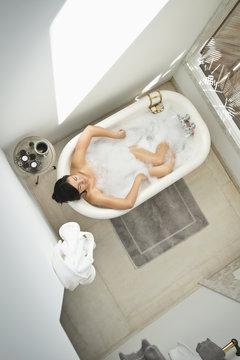 Woman having bubble bath in bathroom