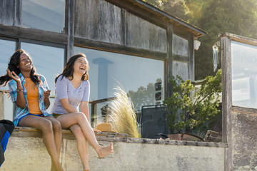 Laughing women sitting in backyard