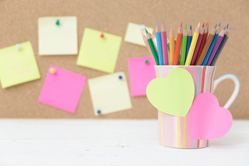 Still life color pencils in colorful cup on wooden table and post it note for insert your text - vintage effect style picture