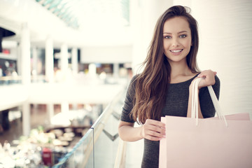 Beautiful woman with shopping bags in big mall.