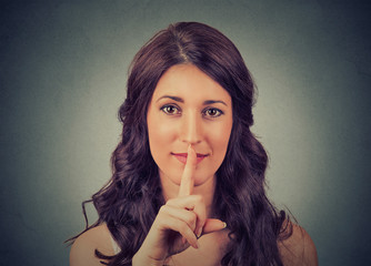 silence gesture. closeup of young woman holding placing finger on lips