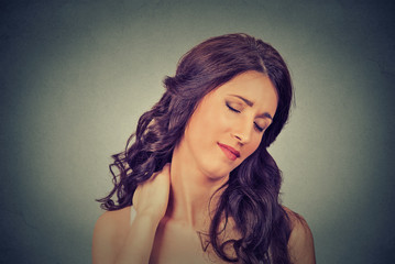 tired woman massaging her painful neck
