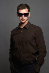 fashion portrait of handsome man in sunglasses.Brutal guy