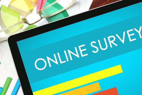 Online Survey written on a tablet. Web marketing concept.