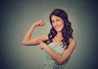 Fit young healthy model woman flexing muscles showing her strength