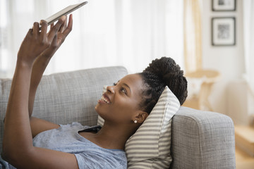 Black woman using digital tablet on sofa