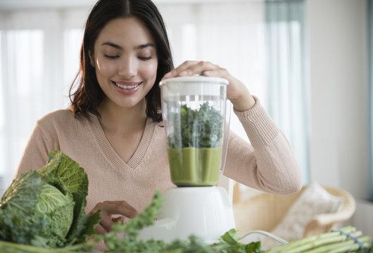 Hispanic woman blending healthy smoothie