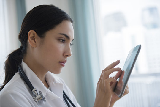 Hispanic doctor using digital tablet