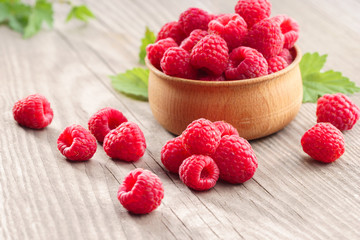 Raspberries in bowl on wooden table. Close up, high resolution product. Harvest Concept