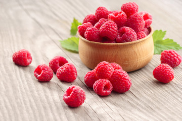 Deluxe Raspberries in bowl on wooden table. Close up, high resolution product. Harvest Concept