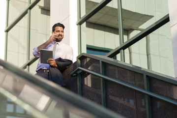Indian businessman talking on cell phone on steps