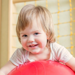 Smiling baby playing with gymnastic ball.