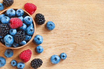 Heap of sweet tasty berries on wooden table. Close up, top view, high resolution product. Harvest Concept