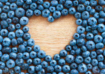 Heart shape made of premium Blueberries on wooden background. Close up, top view, high resolution product. Harvest Concept