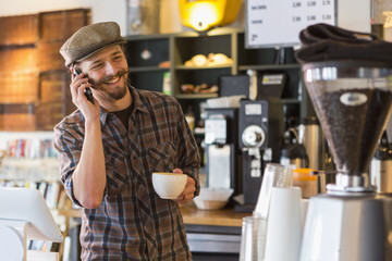 Caucasian man talking on cell phone in cafe