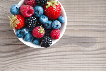 Mixed berries in plate on rustic wooden background. Close up, top view, high resolution product. Harvest Concept