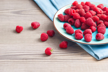 Ceramic plate with raspberries at old wooden table. Close up, high resolution product. Harvest Concept