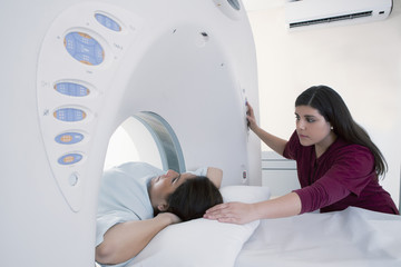 Hispanic nurse examining patient in MRI machine