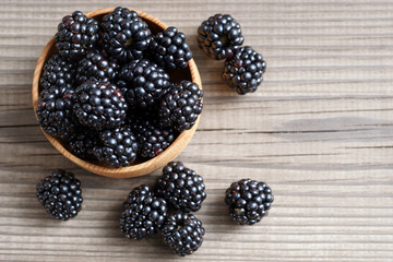 Deluxe blackberries in bowl on wooden background. Close up, top view, high resolution product. Harvest Concept