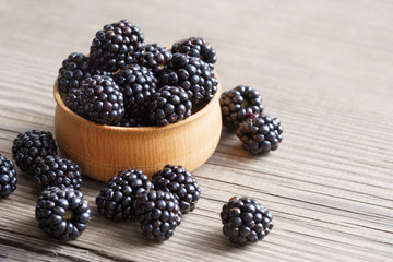 Blackberries in bowl on wooden background. Close up, high resolution product. Harvest Concept