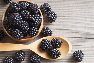 Healthy blackberries in bowl on wooden background. Close up, top view, high resolution product. Harvest Concept