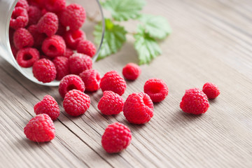 Fresh raspberries in bowl on wooden table. Close up, high resolution product. Harvest Concept