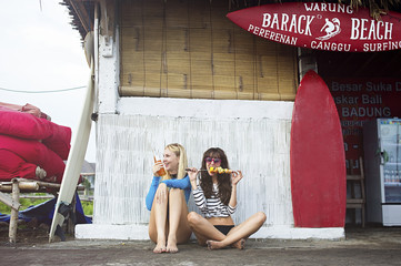 Caucasian women eating at surf hut on beach