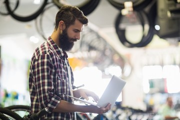 Bike mechanic checking laptop