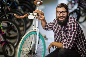 Bike mechanic crouching next to a bicycle