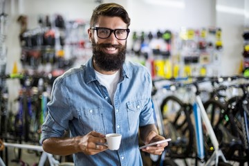 Bike mechanic checking at smartphone and having coffee