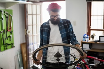 Bike mechanic looking at wheel