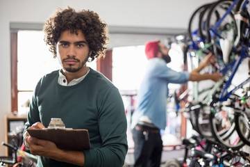 Hipster bike mechanic holding a clipboard