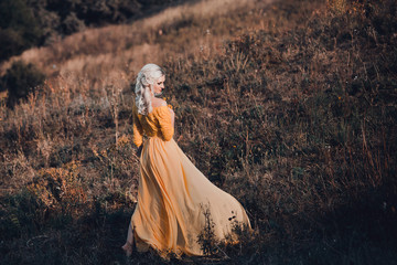 beautiful lady in a long yellow dress walks among the enchanted forest , princess, queen, fantastic Fotoshoot fashionable toning, creative color.