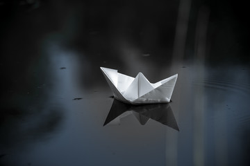 paper boat sailing on water surface at sunset