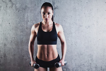 Beautiful muscular woman doing exercise with dumbbells on a gray background.