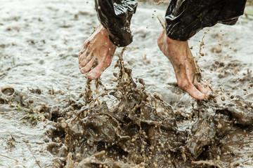 Feet splashing in muddy water