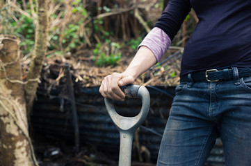 Young woman resting hand on spade
