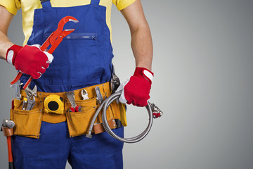 plumber with tool belt isolated on gray with copy space