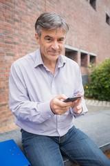 Portrait of smiling professor using mobile phone in campus